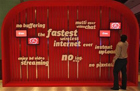 A man touches a screen on a Bharti Airtel advertisement billboard during the launch ceremony for 4G services in Kolkata April 10, 2012. REUTERS/Rupak De Chowdhuri