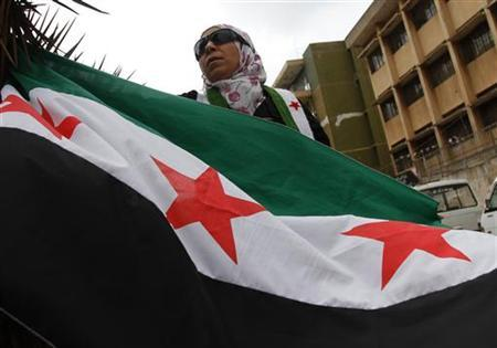 A female protester holds the Syrian opposition flag during a demonstration against Syria's President Bashar al-Assad in Tripoli, northern Lebanon, April 20, 2012. REUTERS/Omar Ibrahim