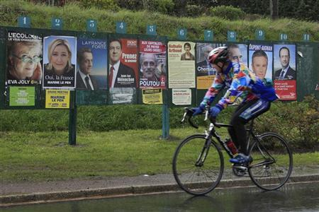A cyclist rides past electoral panels with campaign posters of the candidates for the 2012 French presidential election, in Mons en Pevele near Lille, April 21, 2012. France's presidential candidates observed a one-day truce on Saturday on the eve of a first-round vote expected to send President Nicolas Sarkozy and Socialist challenger Francois Hollande through to next month's runoff. REUTERS/Pascal Rossignol