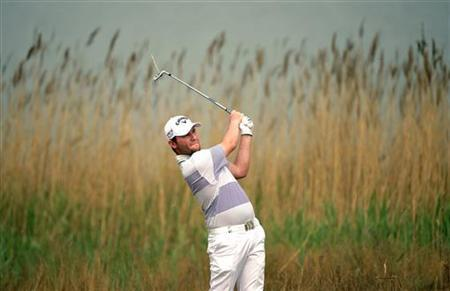 Branden Grace of South Africa watches his shot during the final round of the European PGA Tour China Open at Binhai Lake Golf Club in Tianjin municipality, April 22, 2012. REUTERS/Paul Lakatos/OneAsia/Handout