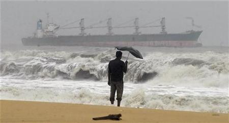 A man holding an umbrella watches large waves on the Marina beach as a cargo ship passes in Tamil Nadu December 30, 2011. REUTERS/Babu/Files