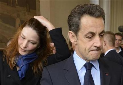 France's President and UMP party candidate for the 2012 French presidential election, Nicolas Sarkozy, holds his ballot near his wife Carla Bruni-Sarkozy, in the first round of 2012 French presidential election at a polling station in Paris, April 22, 2012. REUTERS/Eric Feferberg/Pool