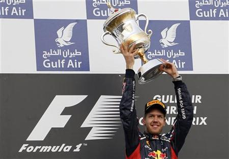 Red Bull Formula One driver Sebastian Vettel of Germany lifts his trophy after winning the Bahrain F1 Grand Prix at the Sakhir circuit in Manama April 22, 2012. REUTERS/Steve Crisp