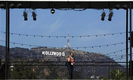 A woman talks on her cellular phone in front of the Hollywood sign prior to the 84th Academy Awards in Hollywood, California February 23, 2012. REUTERS/Lucas Jackson