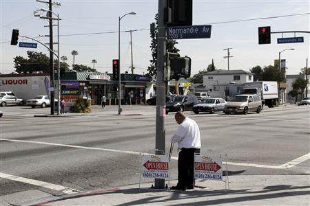 An employee of a real estate agency places ''open house'' signs on the corner of Florence and Normandie in Los Angeles, California, April 4, 2012. REUTERS/Jonathan Alcorn