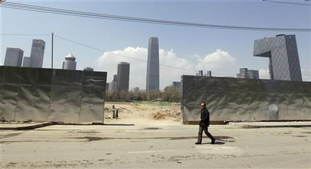 A man walks past a construction site in Beijing's central business district April 13, 2012. REUTERS/Jason Lee