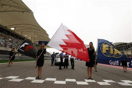 Air Gulf flight attendants holds Bahraini, Formula One and FIA (Federation Internationale de l'Automobile) flags before the Bahrain F1 Grand Prix at the akhir circuit in Manama April 22, 2012. REUTERS/Hamad I Mohammed