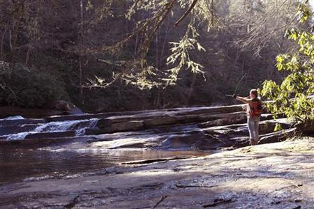 A woman draws on a bow beside a stream at DuPont State Recreational Forest in this undated handout released to Reuters on April 17, 2012. REUTERS/Bill Russ/North Carolina Division of Tourism Sports and Film Development/Handout