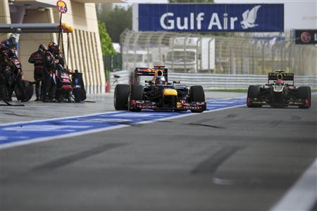Red Bull Formula One driver Sebastian Vettel (L) of Germany leaves his garage after a pit stop as Lotus F1 Formula One driver Romain Grosjean of France drives in the pit lane during the Bahrain F1 Grand Prix at the Sakhir circuit in Manama April 22, 2012. REUTERS/Dimitar Dilkoff/Pool