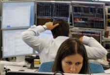 Трейдеры работают в торговом зале инвестиционного банка в Москве, 9 августа 2011 года. Российские фондовые индексы нивелировали в первые минуты торгов понедельника повышение предыдущей сессии на фоне снижения биржевых индикаторов на зарубежных рынках.  REUTERS/Denis Sinyakov