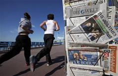 El Ibex-35 se agregaba el lunes a las pérdidas de las principales plazas europeas tras el resultado de la primera vuelta de las elecciones en Francia, a lo que se sumaba la preocupación por la debilidad de la economía española. En la imagen, dos personas pasan corriendo junto a un puesto de periódicos con los resultados electorales franceses en la portada el 23 de abril de 2012 en Niza. REUTERS/Eric Gaillard