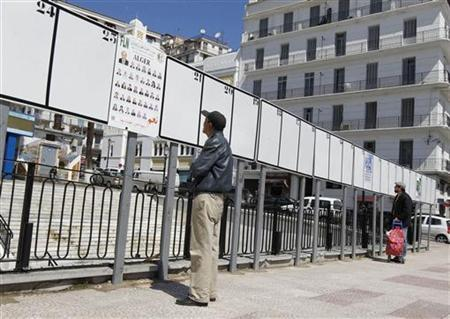 People look at electoral posters in Algiers April 16, 2012. . REUTERS/Louafi Larbi