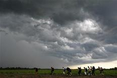 """Люди, приехавшие на фестиваль """"Пустые холмы"""", идут по полю в поселке Булгаково, 11 июня 2009 года. Установившаяся в Москве теплая и дождливая погода сохранится в столице и в течение рабочей недели, ожидают синоптики. REUTERS/Denis Sinyakov"""