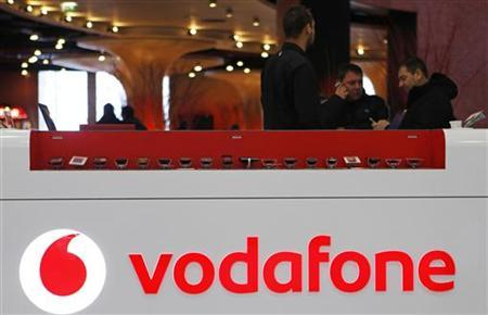 The Vodafone logo is seen at the counter of the shop as customers look at mobile phones in Prague February 7, 2012. REUTERS/David W Cerny