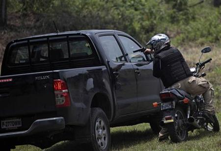 A robbery scene on a motorcycle is re-enacted during an exhibition at the Special Weapons And Tactics (SWAT) course graduation, in the Mariscal Zavala military base in Guatemala City April 21, 2012. REUTERS/Jorge Dan Lopez
