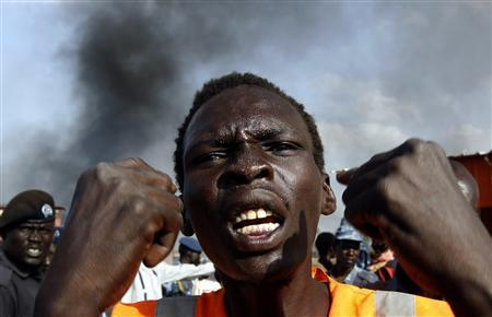 A man gestures at a market burnt in an air strike by the Sudanese air force in Rubkona near Bentiu April 23, 2012. REUTERS/Goran Tomasevic