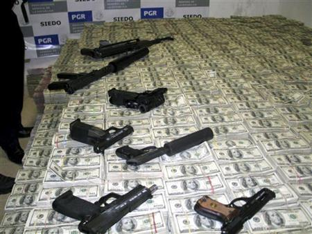 A haul of about 206 million U.S. dollars is seen with confiscated weapons after the money was found stashed in closets, suitcases, and drawers in a house in an upscale neighbourhood of Mexico City March 15, 2007. REUTERS/Procuraduria General de La Republica/Handout