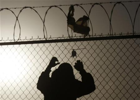 A man watches a U.S. border patrol helicopter from a fence at the border between Mexico and the United States, in Ciudad Juarez March 8, 2012. Picture taken March 8, 2012 REUTERS/Jose Luis Gonzalez