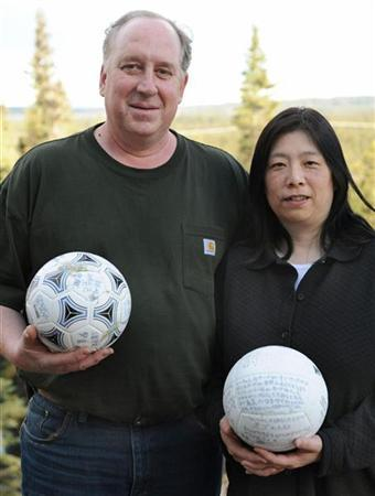 David Baxter (L) and his Japanese wife Yumi pose with a soccer ball (L) which they found at a remote site in the Gulf of Alaska and is likely the first salvageable debris from last year's Japanese tsunami that could be returned to its owner in this photo taken in Alaska April 22, 2012 and released by Kyodo on April 23, 2012. The ball is likely the first salvageable debris from last year's Japanese tsunami that could be returned to its owner, according to the National Oceanic and Atmospheric Administration. The ball was found by Baxter, a technician at a radar station on Middleton Island, a remote site in the Gulf of Alaska. According to a translation provided by Tokyo-based journalists, the ball is from the Osabe School in the Iwate Prefecture, an area that was hit by the devastating tidal wave unleashed on March 11, 2011 by a magnitude 9 earthquake off Japan's northeastern coast. Yumi is holding a volleyball found in a tsunami debris in another town hit by the tsunami and is believed to belong to a 19-year-old girl and bears her name, according to NHK. Picture taken April 22, 2012. Mandatory credit REUTERS/Kyodo