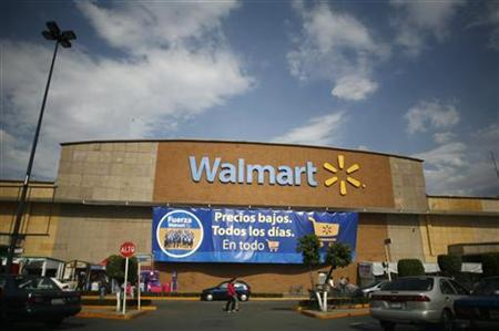 People walk past a Wal-Mart store with a banner reading ''Low prices, every day, in everything'' in Mexico City April 21, 2012. U.S. retail giant Wal-Mart Stores Inc squelched its own internal investigation of allegations made by a former executive of its subsidiary in Mexico that the Mexican division had orchestrated a campaign of bribery to grab market dominance, the New York Times reported on Saturday. REUTERS/Bernardo Montoya