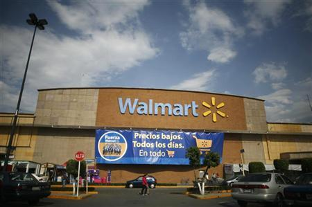 People walk past a Wal-Mart store with a banner reading ''Low prices, every day, in everything'' in Mexico City April 21, 2012. REUTERS/Bernardo Montoya