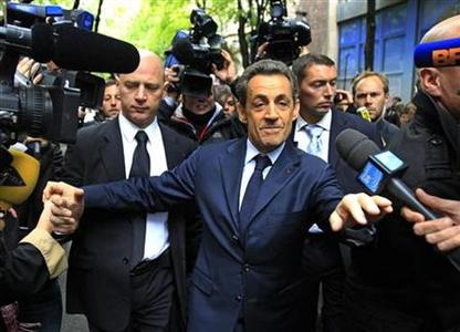 France's President and UMP party candidate for the 2012 French presidential elections Nicolas Sarkozy is surrounded by journalists as he leaves his campaign headquarters in Paris April 23, 2012, the day after the first round of the 2012 French presidential election. REUTERS/Yves Herman
