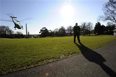 A uniformed Secret Service agent stands guard as Marine One lifts off the South Lawn of the White House in Washington DC December 10, 2011. REUTERS/Mike Theiler