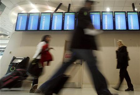 Holiday travellers pass by a row of arrival and departure screens at Hartsfield-Jackson International Airport in Atlanta, Georgia, November 25, 2009.  REUTERS/Tami Chappell