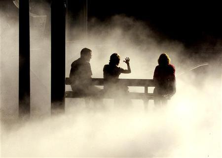 A group of office workers chat whilst sitting on a chair as mist from a nearby artwork piece surrounds them in the centre of the city of Sydney March 29, 2001. REUTERS/David Gray
