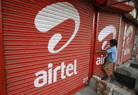 A boy closes the shutter of a shop painted with an advertisement for Bharti Airtel in Ahmedabad May 5, 2011. REUTERS/Amit Dave/Files