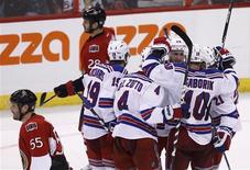 New York Rangers players celebrate a goal by Brad Richards as Ottawa Senators' Sergei Gonchar (55) and Zenon Konopka skate off the ice during the second period of Game 6 of their NHL Eastern Conference quarter-final playoff hockey game in Ottawa, April 23, 2012. REUTERS/Chris Wattie