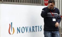Мужчина курит рядом с логотипом Novartis AG перед заводом компании в Базеле, 25 октября 2011 года. Швейцарский фармацевтический концерн Novartis AG сохранил прогноз снижения прибыльности в 2012 году на фоне перерыва в работе фабрики в штате Небраска и высокой базы прошлого года для отделения Sandoz.  REUTERS/Arnd Wiegmann