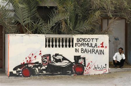 A man smokes next to a wall with anti-Formula One graffiti in a village in Diraz, west of Manama early April 22, 2012. REUTERS/Hamad I Mohammed