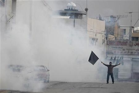An anti-government protester waves a black flag as he is engulfed by a cloud of tear gas fired by riot police during clashes after the funeral procession of Salah Abbas Habib in the district of al-Bilad al-Qadeem in the capital Manama April 23, 2012. REUTERS/Hamad I Mohammed