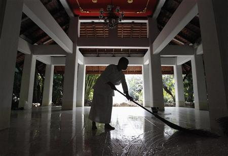 A Buddhist nun cleans the floor after flood waters receded at the Sathira-Dhammasathan Buddhist meditation centre in Bangkok November 21, 2011. REUTERS/Sukree Sukplang