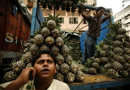 A pineapple fruit seller speaks on a mobile phone as he awaits customers at a wholesale market in Kolkata April 2, 2008. REUTERS/Jayanta Shaw/Files