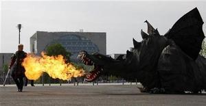 """Актер сражается с механическим драконом для рекламы шоу """"Arena Temporis"""" в Берлине, 29 апреля 2009 г. Умный, кровожадный дракон, пожилой вампир и герой сериала """"Beverly Hillbilly"""" оказались в числе самых богатых вымышленных героев, согласно новому рейтингу Forbes. REUTERS/Fabrizio Bensch"""
