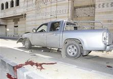 A pool of blood is pictured next to a damaged car after a bomb exploded in Damascus in this handout released by Syria's national news agency SANA April 24, 2012. REUTERS/SANA/Handout