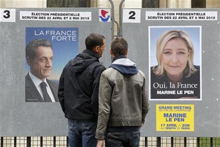 People stop to read the official campaign posters for candidates in the French presidential election: Nicolas Sarkozy, France's President and UMP candidate and Marine Le Pen, France's National Front head in Paris, April 9, 2012. REUTERS/Benoit Tessier