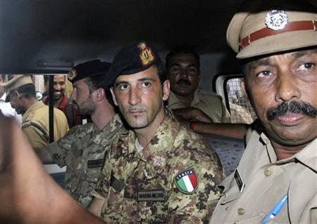 Salvatore Girone (centre L) and Latorre Massimiliano (3rd R), members of the navy security team of Napoli registered Italian merchant vessel Enrica Lexie, sit in a police vehicle after they appeared before a court at Kollam in Kerala March 5, 2012. REUTERS/Sivaram V