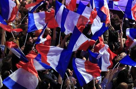 France's UMP party supporters wave French flags at La Mutualite meeting hall in Paris where France's President and UMP party candidate for the 2012 French presidential elections Nicolas Sarkozy delivered his address after early results in the first round vote of the 2012 French presidential election April 22, 2012. REUTERS/Yves Herman