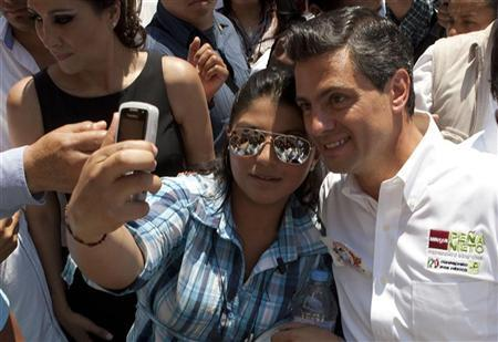 A woman takes a picture of herself and Enrique Pena Nieto, presidential candidate of the opposition Institutional Revolutionary Party (PRI), during a political rally in Queretaro April 12, 2012. REUTERS/Demian Chavez