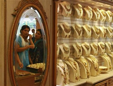 A woman is reflected in a mirror as she tries a gold earring inside a gold jewellery showroom in the Kochi April 16, 2012. REUTERS/Sivaram V