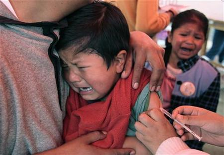A child reacts while receiving a vaccination against measles and rubella in La Paz, April 15, 2012. REUTERS/David Mercado