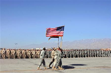 U.S. soldiers carry flags of the U.S. and Afghanistan during a Memorial Day ceremony at the Bagram airbase north of Kabul May 28, 2006. REUTERS/Ahmad Masood/Files