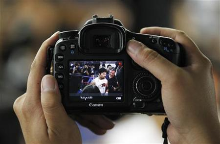 A member of the media uses a Canon SLR camera to record video as congressman and boxer Manny Pacquiao of the Philippines is interviewed during a media workout at Wild Card Boxing Club in Los Angeles October 26, 2011. REUTERS/Danny Moloshok