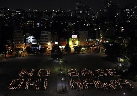 Demonstrators holding candles form letters reading ''No Base Okinawa'' during a rally in Tokyo April 25, 2010. REUTERS/Yuriko Nakao (JAPAN - Tags: MILITARY POLITICS)