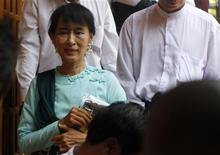 Myanmar pro-democracy leader Aung San Suu Kyi smiles at her supporters as she leaves a monastery after attending a religious ceremony at Yangon April 24, 2012. REUTERS/Minzayar