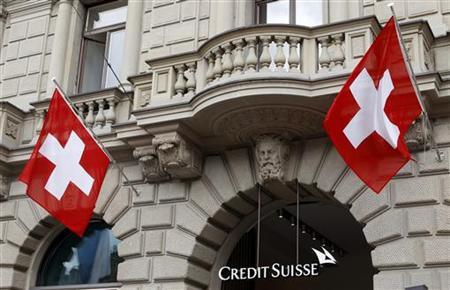 Switzerland national flags fly beside the logo of Swiss bank Credit Suisse (CS) at the company's headquarters in Zurich April 13, 2012. REUTERS/Arnd Wiegmann