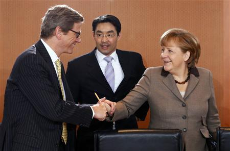 German Foreign Minister Guido Westerwelle (L) welcomes Chancellor Angela Merkel (2nd R), as she arrives with Economy Minister Philipp Roesler to a cabinet meeting in Berlin April 25, 2012. REUTERS/Fabrizio Bensch